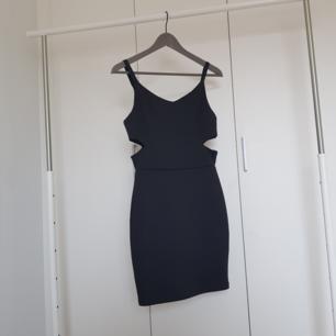 Svart klänning med håll på sidan. Använd typ 4 gånger, en av axel banden är lite sönder men den sitter fast kvar. Du betalar frakt.