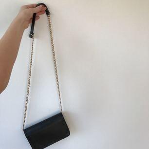 Snygg liten clutch med guldig kedja som axelrem. Väskan har ett stort fack och tre små, samt en