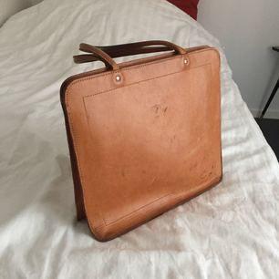 Ljusbrun läderväska från okänt märke.  I använt skick med lite fläckar och en trasig sömm, därav det låga priset.  31 cm bred och 28 cm djup, bara ett stort fack.