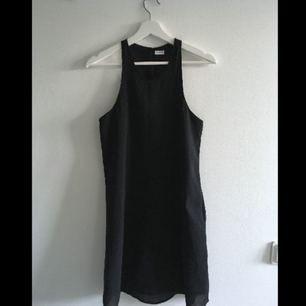 En klänning med dubbelt tyg. Översta är genomskinligt och det under skyddar insyn. En knäppning bak i nacken. En riktigt skön och svängig klänning.