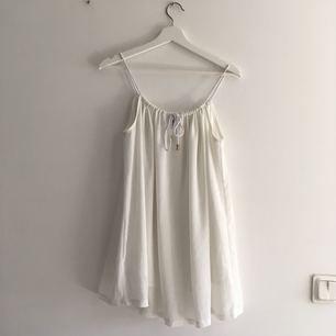 En vit härlig kort klänning, kan alternativt användas som ett linne