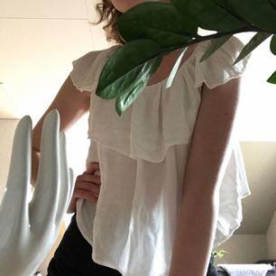 En vit blus som man kan använda off shoulder eller som på bilden. Lite skrynklig men kan strykas innan frakt. Jättefin till sommaren!