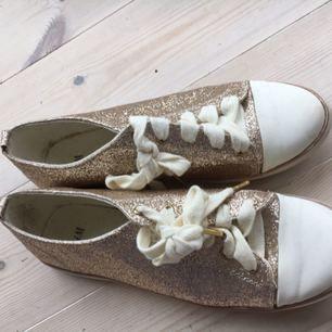 🌷Guld glittriga sneakers i storlek 40 från H&M. Sparsamt använda men har en blek fläck på tån av ena skon, så priset kan diskuteras. Hund ingår inte. 🌷