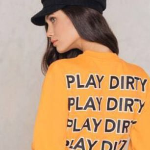 """Säljer en orange sweater från nakd med """"play dirty"""" tryck på ryggen, använd endast 1 gång! Köparen står för frakten som ligger på 45kr, kan även mötas upp i centrala Göteborg!"""
