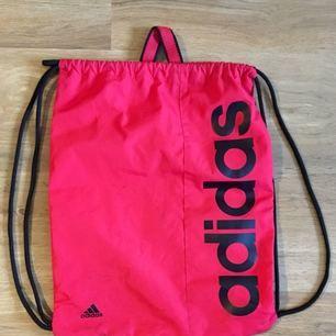 Gympapåse från Adidas. Orange/röd.