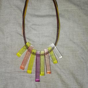 Halsband i kort modell med hänge i olika färger.