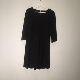En liten svart klänning med en liten drag kedja bakom ryggen, den passar dig som ska ha en utekväll.