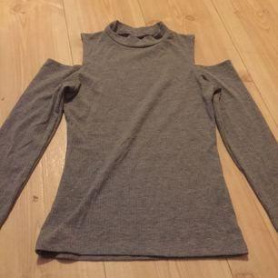 En grå långärmad tröja som gör så att man ser lite av axlarna, sitter super fint på !