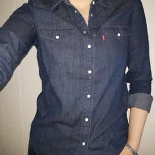 Super snygg mörkblå Levi's skjorta med vita marmor liknande knappar i storlek S men den passar även på mig som har storlek M. I super fint skick. Köparen står för frakt, kan även mötas upp i Karlstad området. Priset på skjortan kan diskuteras.