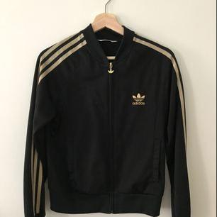 Adidas tröja med guldränder (utgått) Passar ca en small. Några trådar har lossnat, därav priset. Kan skickas mot fraktkostnad.