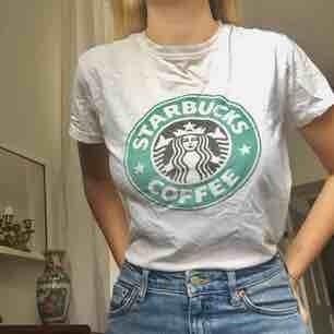 Starbucks t-shirt köpt i Spanien! Passar XS och S beroende på hur man vill att den ska sitta. Mjukt tyg och trycket försvinner ej i tvätten. Litet hål i ena armhålan. Möts i Stockholm!