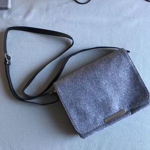 Helt oanvänd handväska i mjukt grått tyg, flera fack och justerbar rem