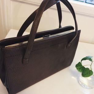 Fabulös mörkbrun handväska! Ca 35cm bred och 20cm hög. Små sidofack för papper och ett mindre fack inuti. Väldigt bra skick och det är med sorg jag säljer denna pärla som jag använt på tok för lite!