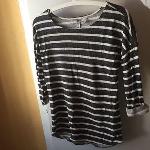 En mjuk mörkgrå och vit randig tröja i strl. XS (passar även mig med 36) knappt använd. Fraktar ej!