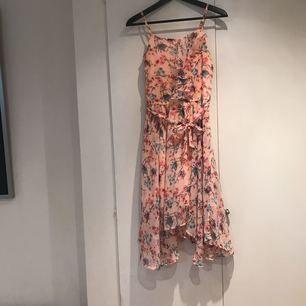 Knälång ljusrosa klänning med tyg som är lite längre på sidorna Med blommor och fjärilar  Väldigt bra skick