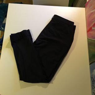 Sköna kostymbyxor från Mango i mörk marinblå. Ankellängd med uppvikt benslut.