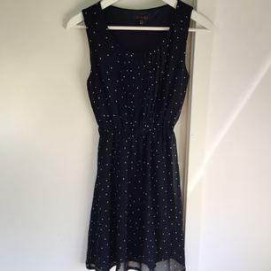 Fin mörkblå klänning med vita prickar. Ett skärp följer med (ej med på bild). Begagnat skick.