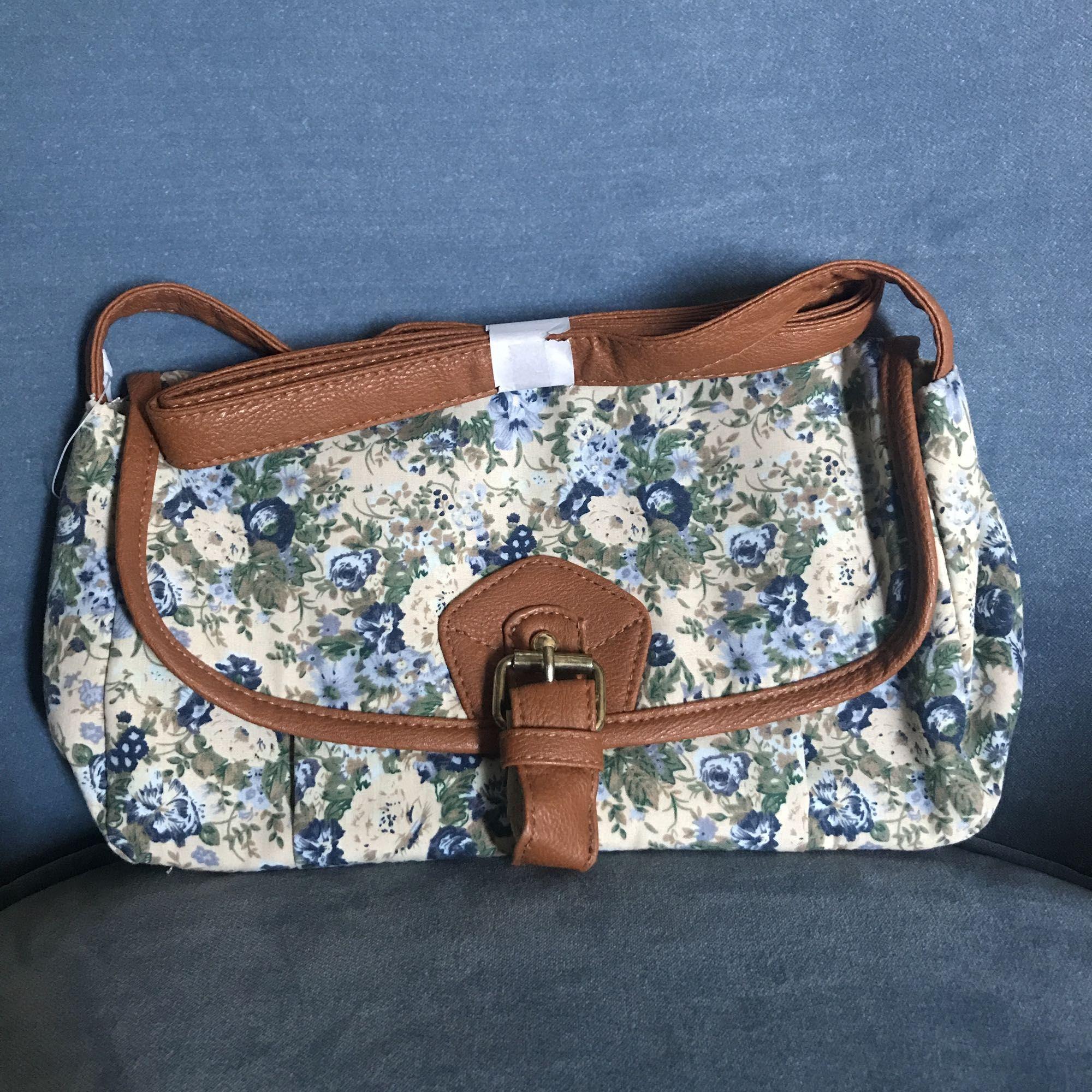 Söt, blommig axelremsväska, kantad av bruna detaljer. Perfekt mellanstorlek. Aldrig använd. Frakt ingår i priset! . Väskor.