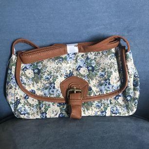 Söt, blommig axelremsväska, kantad av bruna detaljer. Perfekt mellanstorlek. Aldrig använd. Frakt ingår i priset!