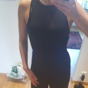 Svart jumpsuit i blankt svart material med som som markerar midjan. Aldrig använd.    Finns i Helsingborg men kan skickas mot fraktkostnad