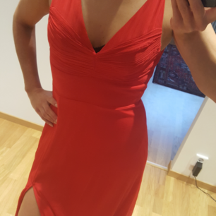 Röd långklänning med slits vid ena benet.  Använd endast 1 gång på en bankett.  Storlek 34   Finns i Helsingborg och kan skickas mot fraktkostnad.