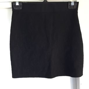 Figurnära kjol med resårband upptill. Utanpå själv kjolen är det ett lager av spetsliknande material vilket ger kjolen lite karaktär. Fint begagnat skick.