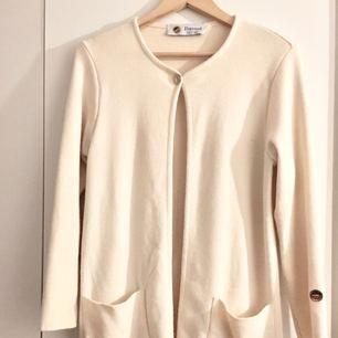 Busnel Petra coat  Härlig kappa i fin ullkvalité från Busnel. Rak passform, och lite tunnare kvalité som försluts med guldfärgade knappar. Busnel-avsändare på vänster ärm. 100% ull. Färg: offwhite