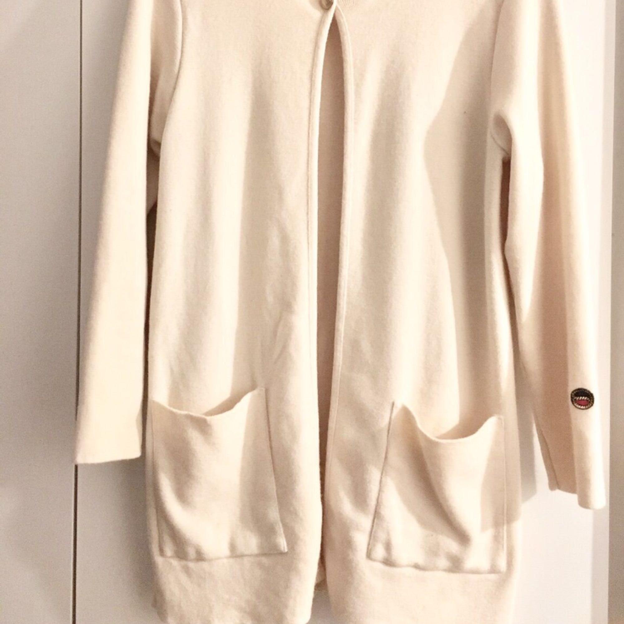 Busnel Petra coat  Härlig kappa i fin ullkvalité från Busnel. Rak passform, och lite tunnare kvalité som försluts med guldfärgade knappar. Busnel-avsändare på vänster ärm. 100% ull. Färg: offwhite. Jackor.