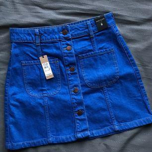 Helt oanvänd jeanskjol från River Island! En riktig färgklick i sommar 🦋🦋   Frakt tillkommer 👏🏼