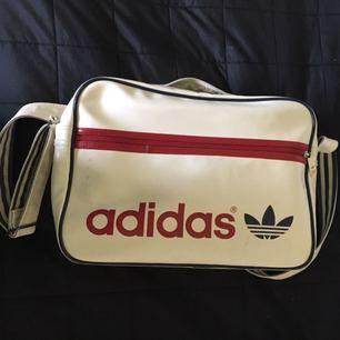 🌹Off-white Adidas axelremsväska med marinblå och röda detaljer. Använd och har därför några märken på ytter- och insidan men annars i bra skick samt har två fack på insidan och ett på utsidan. Köparen står för halva frakten. Priset kan diskuteras