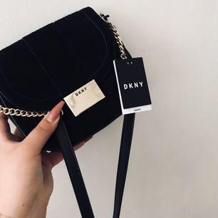 Säljer en helt ny DKNY väska Väskan har gulddetaljer och är i suede-material Axelremsväska  Nypris: 2299:- Prislappen hänger kvar Dustbag medföljer Kan fraktas mot betalning