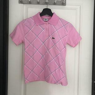 En rosa piké från Lacoste. Köpt på second hand. Den har ett litet hål på sömmen i bak.   Jag kan mötas upp i Mariestad, annars står jag för frakten.
