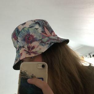 Blommig fiske hatt köpt på forever 21. Använd 1-2 gånger men den är som ny.   Kan mötas upp i Mariestad, annars bjuder jag på frakten.