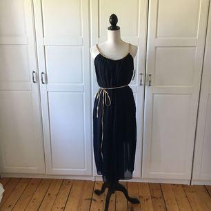 Marinblå vadlång klänning, med guldiga detaljer. Onesize. Aldrig använd. Köparen står för ev frakt.