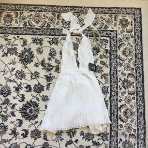 """Vit plisserad klänning i storlek 36, inhandlad på Nelly (Märke """"Stars"""" av Jonas Hallberg). Medföljande """"stelt"""" skärp i krom. Aldrig använd.  Köparen står för ev frakt."""