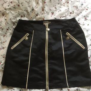 Kjol från Moschino med snygga detaljer i silkigt material, storlek S. Kan mötas upp i Lund, köpare betalar frakt.