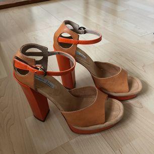 Snygga högklackade skor från Tosca Blu i brunt läder och platåsula i orange. Klackhöjd: 13,5 cm. Knäppning kring vristen. Oanvända, köptes för 1499:- på Nelly. Frakt 29 kr🌿