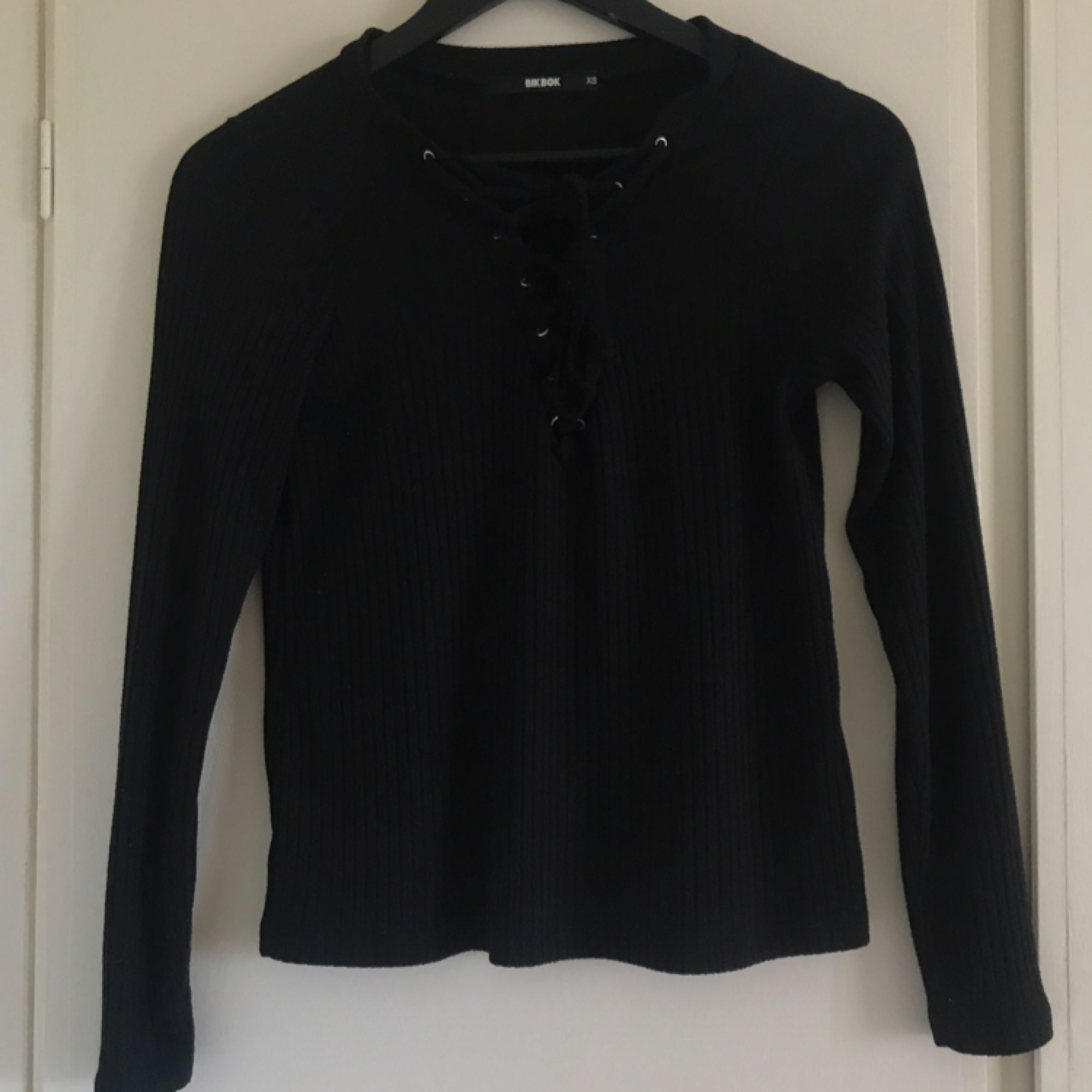 Svart tröja med snörning från BikBok. XS men passar också S. Mycket fint skick. Kan mötas i Norrköping annars står köparen för frakten.. Toppar.