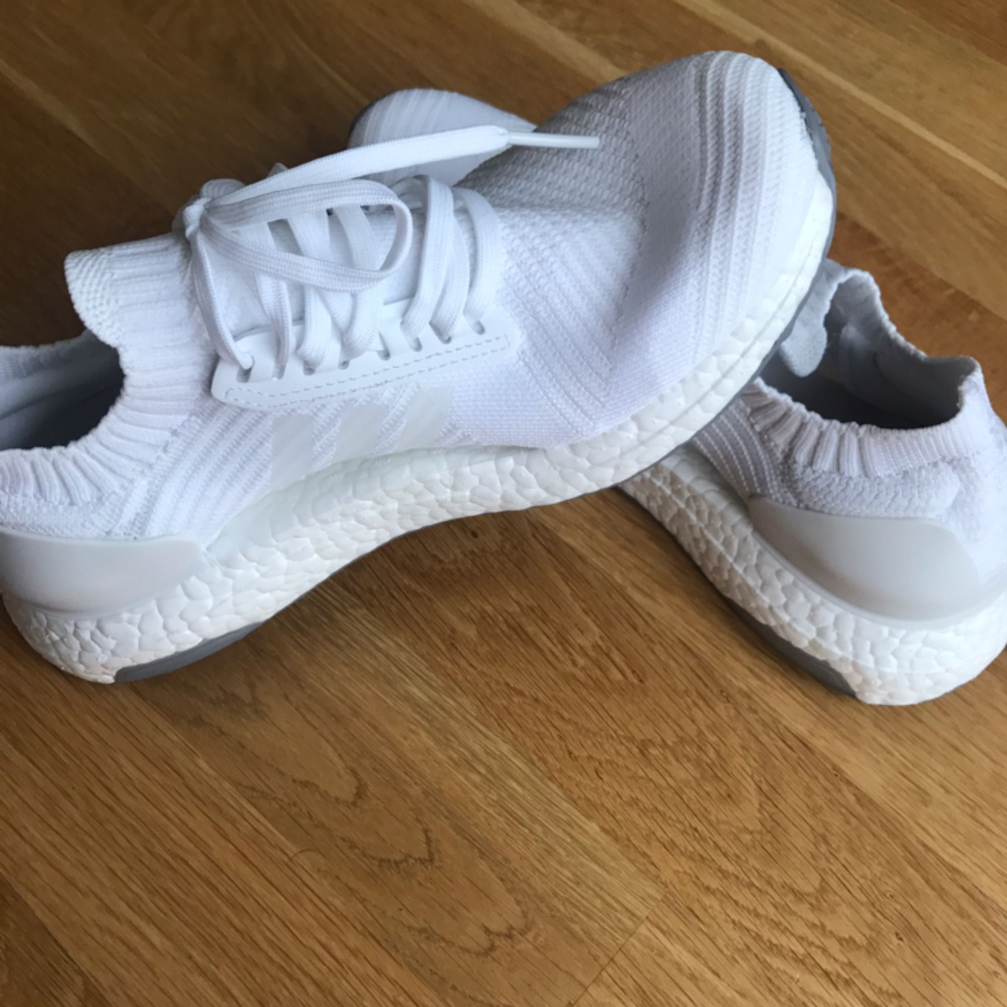 Ett par vita adidas ultraboosts, använd en kort gång. 800kr billigare än original priset. Frakt ingår inte i priset.. Skor.