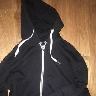 Skön svart munkis med vita detaljer. Två separata framfickor på framsidan.