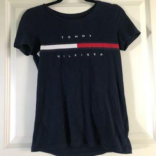 Trendig marinblå Tommy Hiftiger t-shirt med logga på bröstet. Storlek XXS men jag skulle säga att den motsvarar en S. Finns inte att få tag på längre! Frakt tillkommer men kan mötas upp i Stockholm, Tyresö och Nacka!