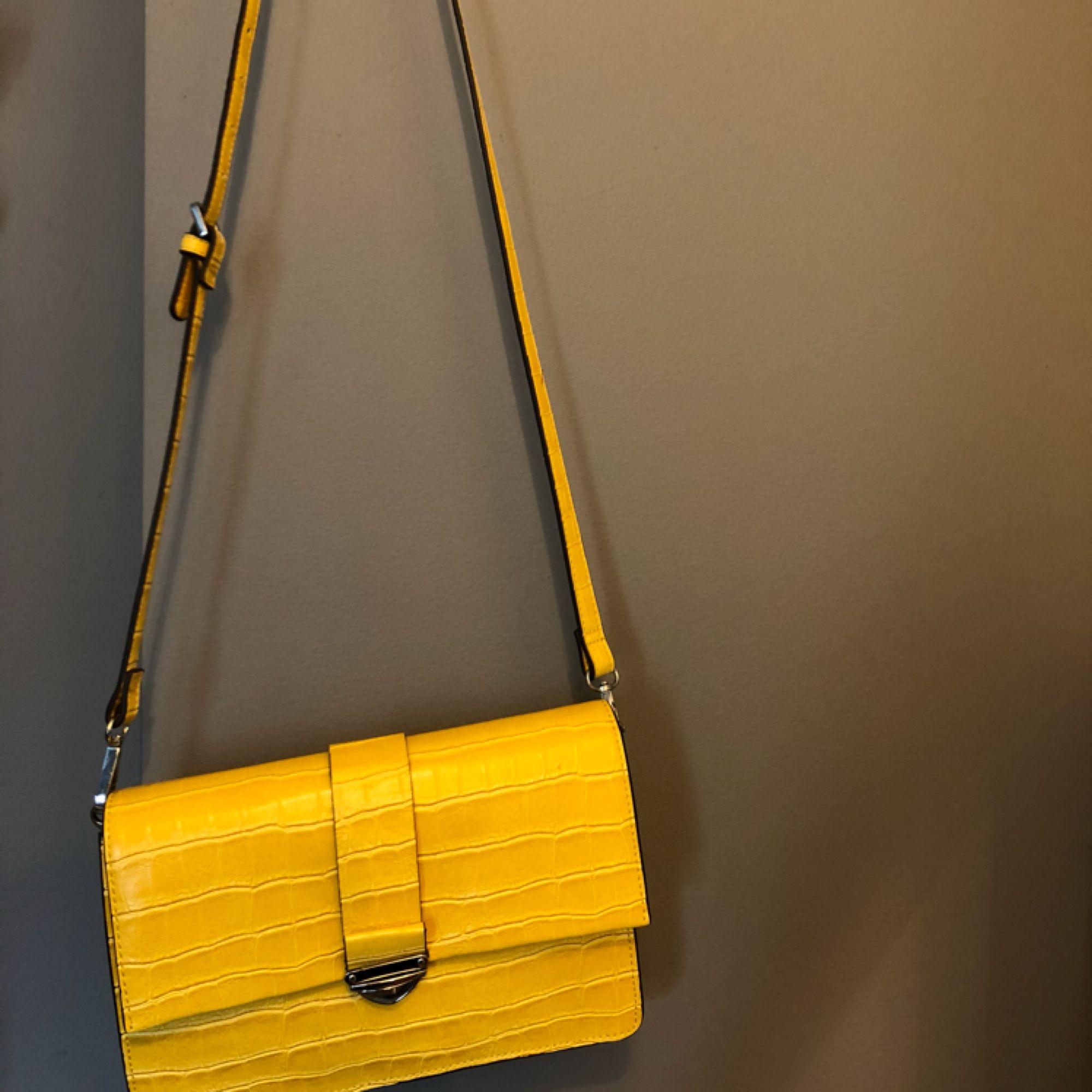 En gul väska från mango. Har använt några gånger men den är ett bra skick. Väskan går till revbenshöjd men längden går att ändra. . Väskor.