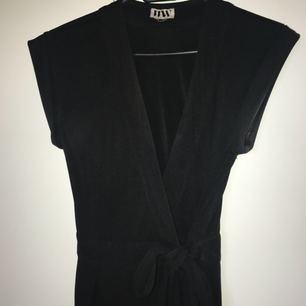 Jumpsuit med långa ben från bubbleroom (make way). V-ringad och med knytband i midjan. Kostym-aktigt material i 100% polyester.