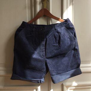 Marinblå mockashorts med klarblått sidenfoder. Fickor i sidan.