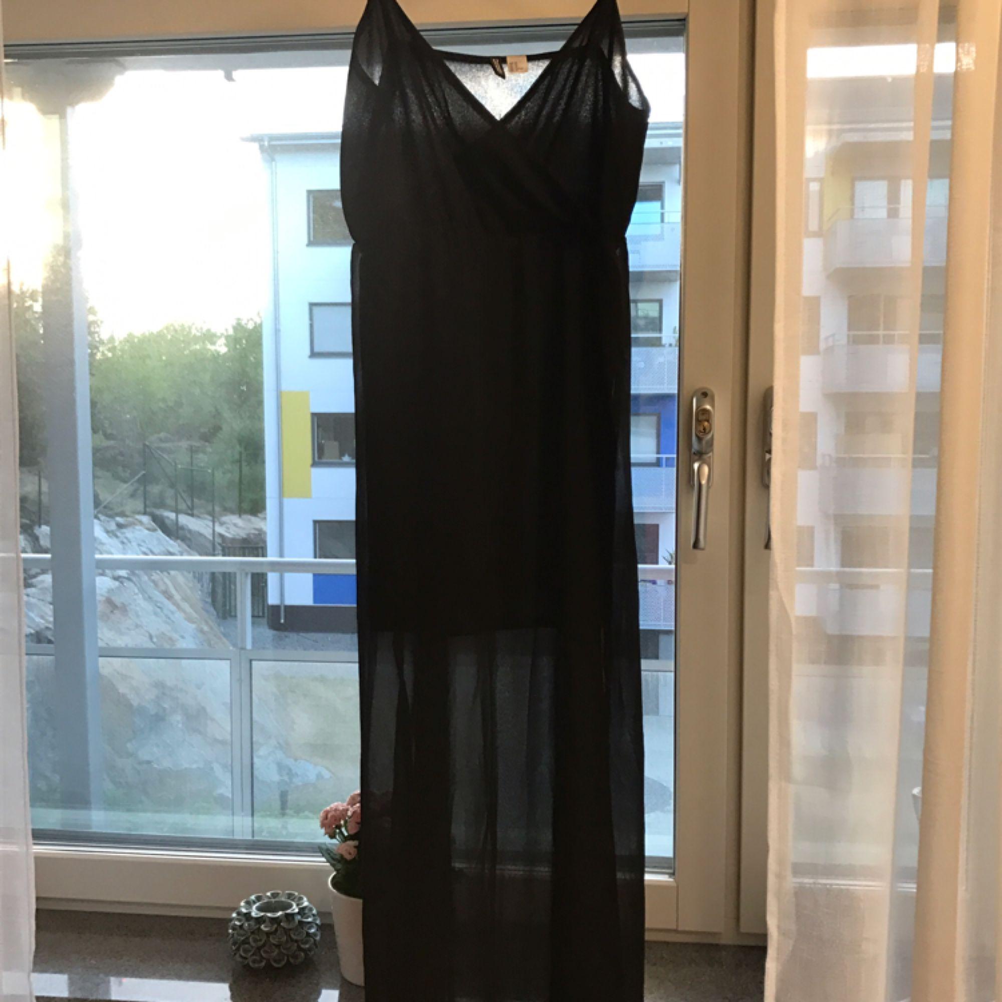 Super snygg svart klänning. Svart transparent tyg ytterst och en kortare inner klänning under så att man inte ser igenom. Väldigt fin och elegant! Sparsamt använd, 1-2 gånger. Lös i passformen. Köparen står för eventuell frakt. . Klänningar.