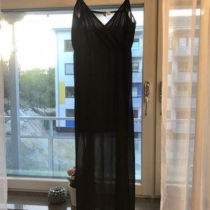 Super snygg svart klänning. Svart transparent tyg ytterst och en kortare inner klänning under så att man inte ser igenom. Väldigt fin och elegant! Sparsamt använd, 1-2 gånger. Lös i passformen. Köparen står för eventuell frakt.