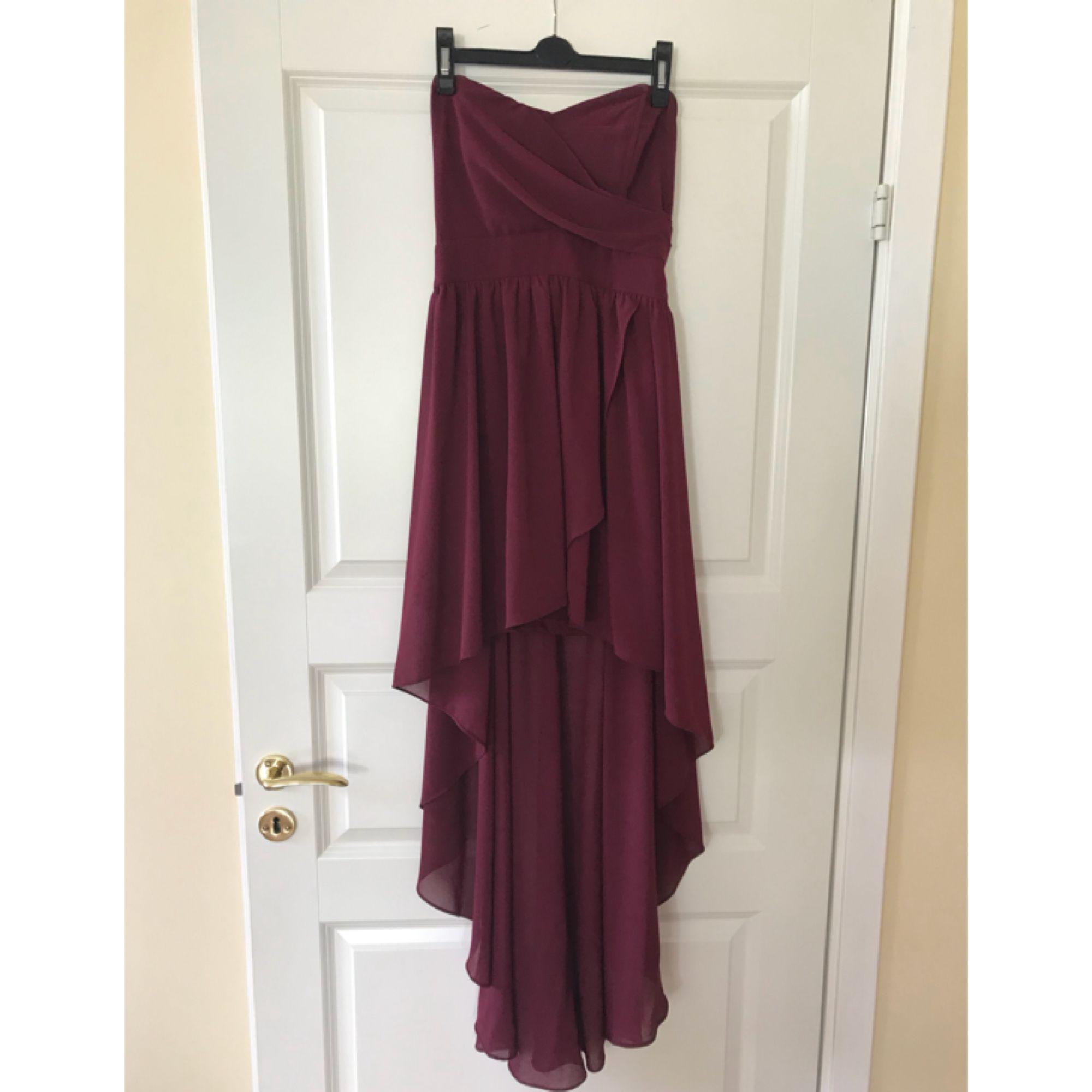 833dee32f7ad Vinröd bandlös klänning, lång bak, kort fram från Topshop. Fint material,  sparsamt