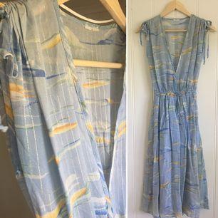 Ljusblå vintage klänning med silvriga lurex tråd. Fint skick.