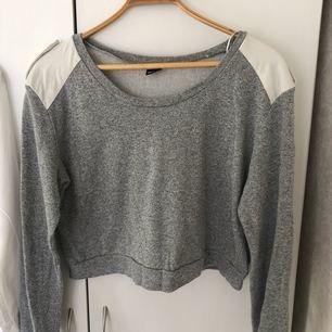 Grå snygg sweatshirt från Gina tricot i storlek L. Mocka imitation på axlarna med knapp. Använd men i fint skick. Frakt tillkommer.