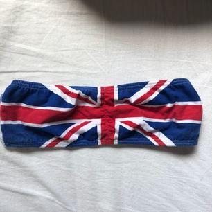 Bandåtopp med engelska flaggan på. Står ingen storlek men sitter som en S. Använd men i fint skick. Frakt tillkommer.